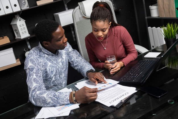 two-young-black-people-discuss-their-business-using-diagrams-sitting-desk-office_88135-7706